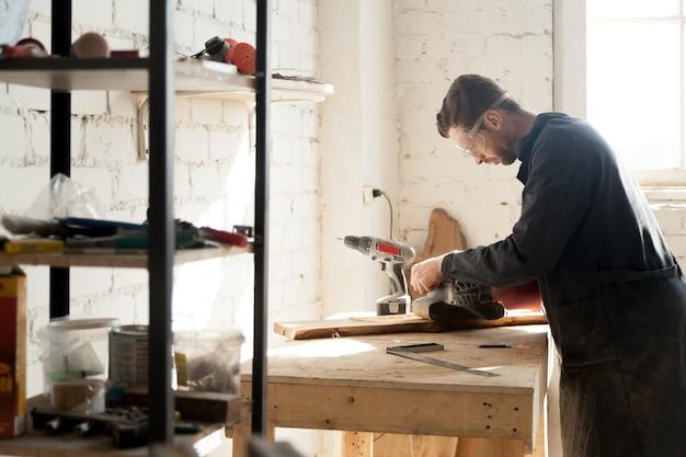 erfahrener junger tischler der mit holz im schreinerei werkstatt drinnen arbeitet download. Black Bedroom Furniture Sets. Home Design Ideas