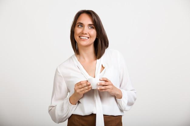 Erfolgreiche frau trinken kaffee und lächeln Kostenlose Fotos