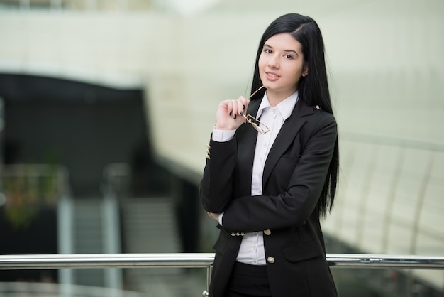 Erfolgreiche geschäftsfrau, die überzeugt und das lächeln schaut Premium Fotos