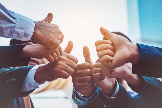 Erfolgreiche geschäftsleute mit daumen hoch und lächelnd, business-team Premium Fotos