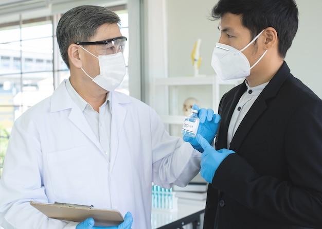 Erfolgreiche reife männliche forscher oder kliniker zeigen dem asiatischen geschäftsmann einen covid19-impfstoff bei der erfindung eines neuen impfstoffs. Premium Fotos