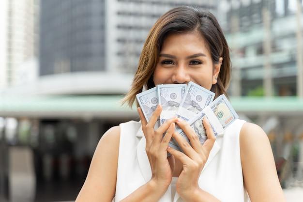 Erfolgreiche schöne asiatische geschäftsfrau, die geld us-dollar rechnungen hält Kostenlose Fotos