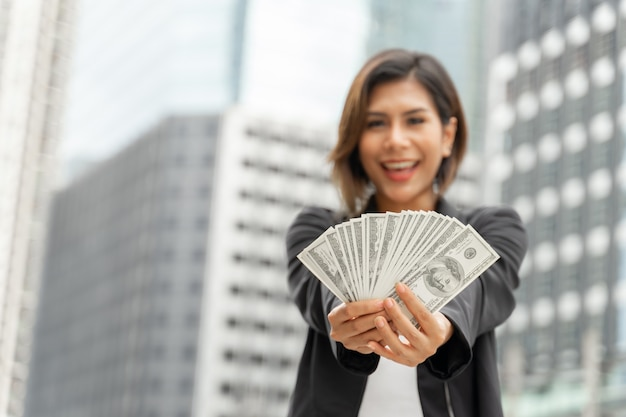Erfolgreiche schöne asiatische geschäftsfrau, die in der hand geld us-dollar rechnungen, geschäftskonzept hält Kostenlose Fotos