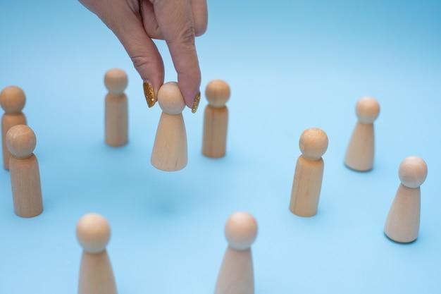 Erfolgreiche teamleiterin, frauenhand, wählt leute aus, die sich von den anderen abheben. Premium Fotos