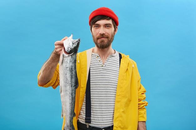 Erfolgreicher bärtiger fischer, der über blauer wand mit seinem fang steht, der glücklichen ausdruck hat. hübscher junger mann, der langen schweren fisch in den händen hält, die stolz und aufgeregt fühlen Kostenlose Fotos
