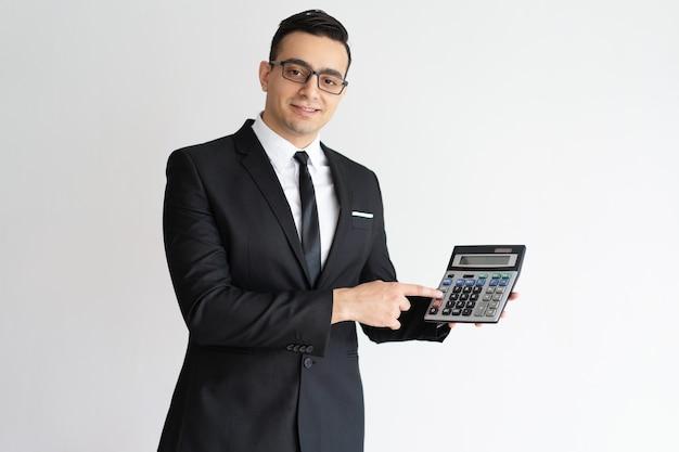 Erfolgreicher finanzier, der taschenrechner verwendet und es kamera zeigt. Kostenlose Fotos
