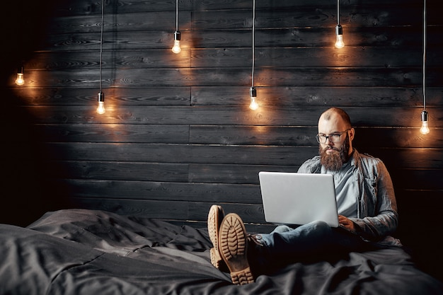 Erfolgreicher freiberuflicher mann des lebensstils mit bart erzielt neues ziel mit laptop im dachbodeninnenraum Premium Fotos