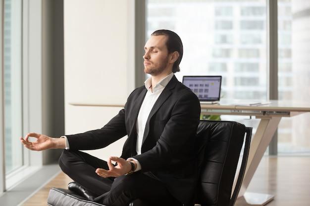 Erfolgreicher geschäftsmann, der am arbeitsplatz meditiert Kostenlose Fotos