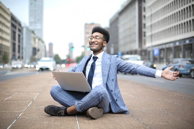 Erfolgreicher geschäftsmann, der beim arbeiten mit seinem laptop in der straße gut sich fühlt Premium Fotos