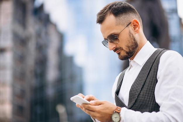 Erfolgreicher geschäftsmann durch den wolkenkratzer, der am telefon spricht Kostenlose Fotos