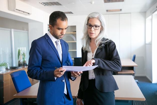 Erfolgreicher geschäftsmann im anzug, der dokument für die unterzeichnung liest, und weiblicher grauhaariger manager in brillen, die auf etwas im bericht zeigen. partner, die im büro arbeiten. geschäfts- und managementkonzept Kostenlose Fotos
