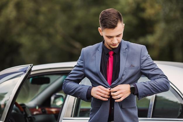 Erfolgreicher geschäftsmann in einem dunklen geschäftsanzug mit einer roten krawatte vor dem hintergrund eines autos. stilvoller mann. modische uhr zur hand. knöpfen sie einen knopf an der jacke zu Premium Fotos