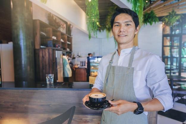 Erfolgreicher hübscher geschäftseigentümer, der mit einem tasse kaffee vor bar steht Premium Fotos