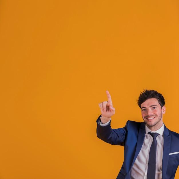 Erfolgreicher junger geschäftsmann, der aufwärts seinen finger gegen einen orange hintergrund zeigt Kostenlose Fotos