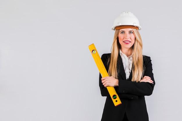 Erfolgreicher junger weiblicher architekt, der gegen grauen hintergrund steht Kostenlose Fotos