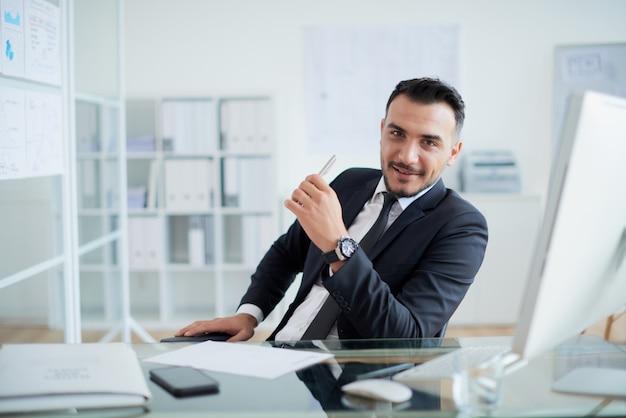 Erfolgreicher kaukasischer geschäftsmann, der am schreibtisch im büro und im lächeln sitzt Kostenlose Fotos