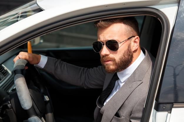 Erfolgreicher kaukasischer mann im formellen anzug, der ein auto fährt Premium Fotos