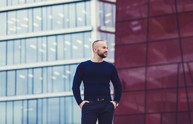 Erfolgreicher mann auf einem gebäudehintergrund Premium Fotos