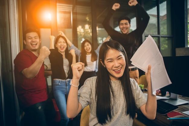 Erfolgreiches glückgefühl des asiatischen jüngeren freiberuflichen teamwork-jobs Premium Fotos