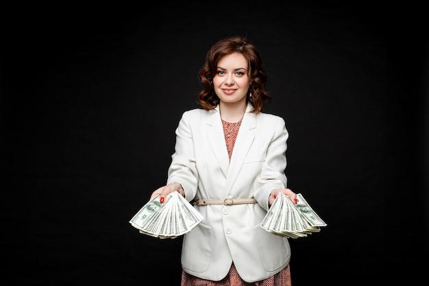 Erfolgreiches stilvolles brünettes modell mit geld in händen. Kostenlose Fotos