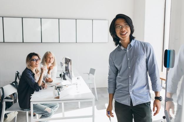 Erfreulicher asiatischer geschäftsmann, der flipchart mit lächeln betrachtet, das im konferenzsaal steht. charmante blonde studentinnen mit laptops beobachten junge lehrer an bord schreiben. Kostenlose Fotos