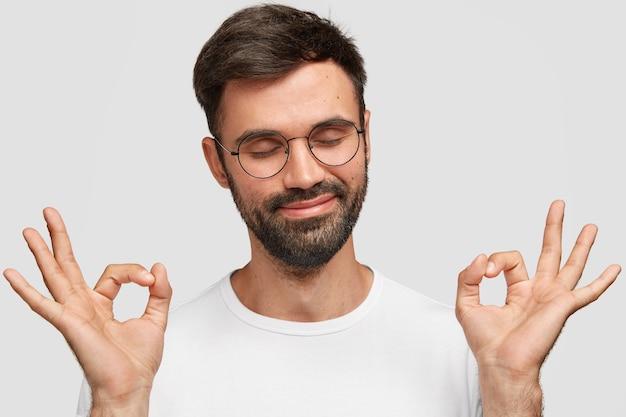 Erfreulicher attraktiver mann mit dickem dunklem bart, macht mit beiden händen eine gute geste, zeigt seine zustimmung Kostenlose Fotos