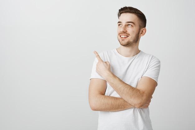 Erfreulicher hübscher junger mann im weißen t-shirt, der finger oben links zeigt Kostenlose Fotos