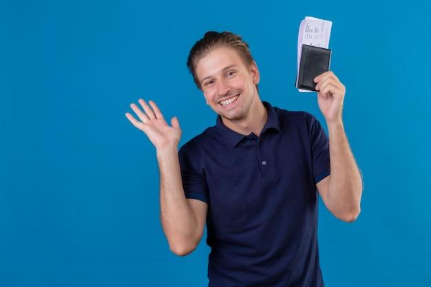 Erfreulicher junger hübscher reisender mann, der flugtickets hält, die fröhlich betrachten kamera, die mit der hand winkend steht, die über blauem hintergrund steht Kostenlose Fotos