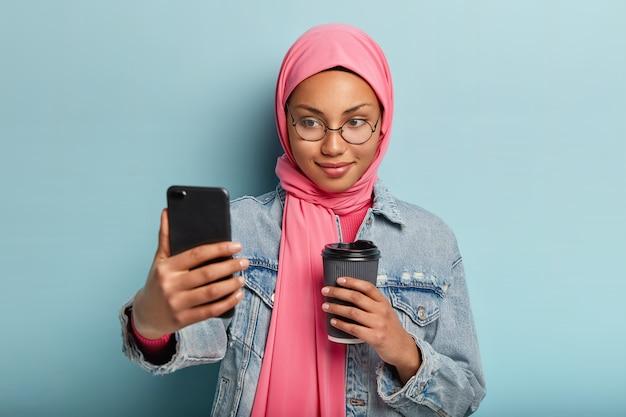 Erfreut angenehm aussehendes muslimisches mädchen trinkt kaffee zum mitnehmen, macht selfie-porträt oder videoanruf, gekleidet in stilvolle jeansjacke und hijab, teilt bilder mit anhängern in sozialen netzwerken Kostenlose Fotos