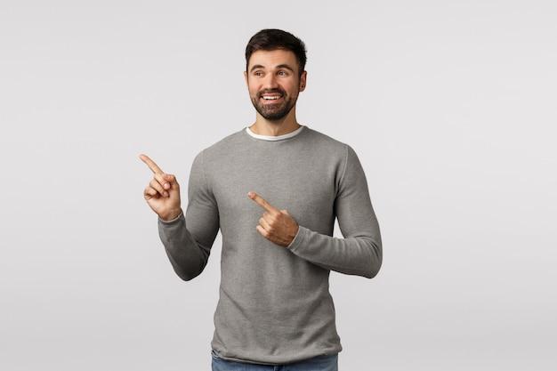 Erfreut charmante glückliche junge gut aussehender mann, erwachsener in grauer strickjacke, zeigt nach links schauen, beobachten süße szene, ausgewählte variante, sehen gute wahl, glücklich und bezaubert, zufrieden lächelnd Premium Fotos