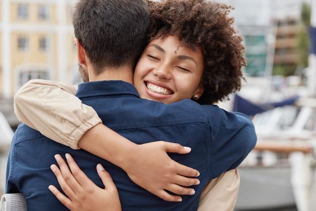 Erfreut glücklich lächelnde afroamerikanerin verabschiedet sich von freund, umarmt warm Kostenlose Fotos