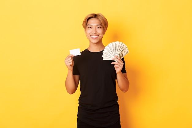 Erfreut hübscher asiatischer kerl, der geld und kreditkarte zeigt, glücklich lächelnd, stehende gelbe wand Kostenlose Fotos