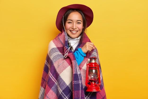 Erfreut lächelnde asiatische frau in plaid gewickelt, hält kleine gaslaterne, trägt hut, posiert vor gelbem studiohintergrund Kostenlose Fotos
