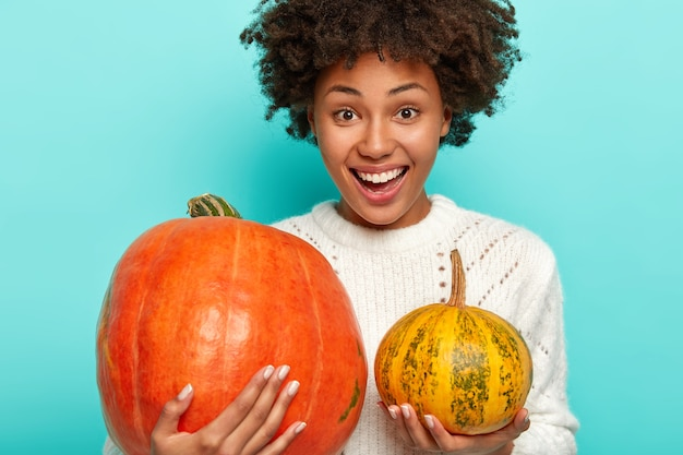 Erfreut lächelnde lockige frau wählt kürbis für halloween, hält großen und kleinen kürbis, trägt weißen pullover Kostenlose Fotos