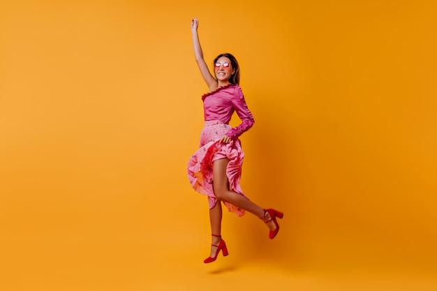 Erfreute, aufgeregte dame in schuhen mit festem urbanem absatz springt in hellrosa seidenkleidung. porträt des mädchens in voller länge mit glattem weichem haar, das im orange raum bewegt Kostenlose Fotos