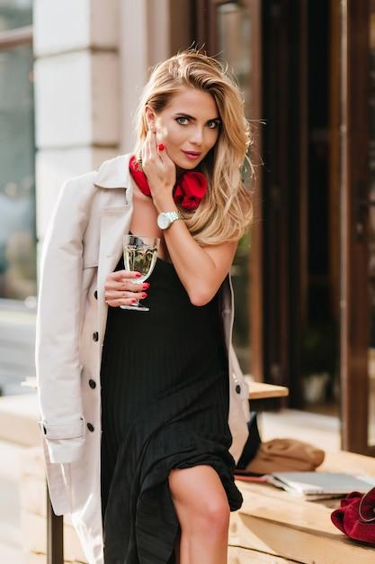 Erfreute blonde frau im langen schwarzen kleid, das mit haaren spielt und lächelt und glas champagner hält. attraktives mädchen im stilvollen mantel, der auf der straße neben kneipe steht und urlaub feiert. Kostenlose Fotos