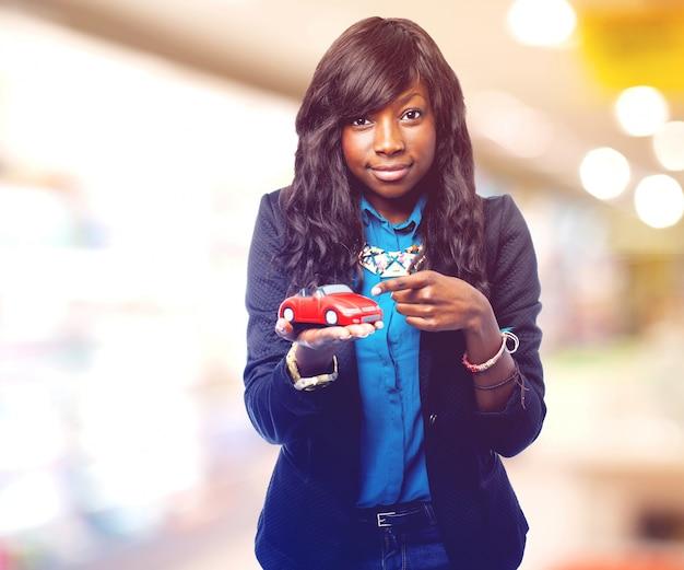 Erfreute frau, ein kleines auto auf ihrer hand zeigt Kostenlose Fotos