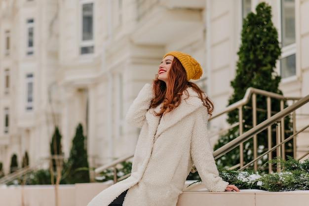 Erfreute gut gekleidete dame, die sich im winter entspannt. außenporträt des fröhlichen ingwermädchens im langen mantel. Kostenlose Fotos