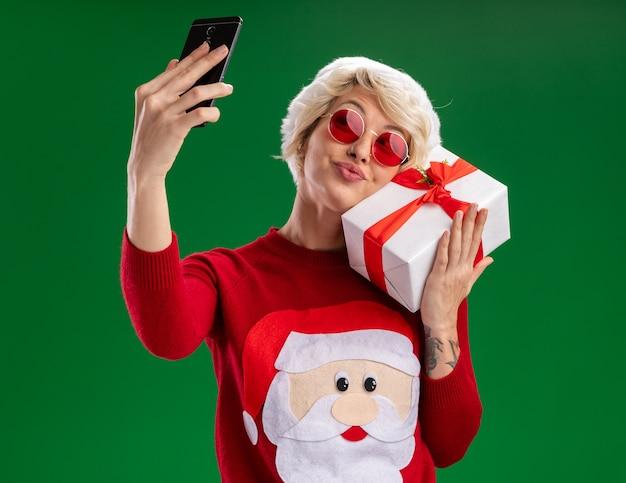 Erfreute junge blonde frau, die weihnachtsmütze und weihnachtsmannpullover des weihnachtsmannes mit der brille hält, die geschenkverpackungsberührungsgesicht mit ihm nimmt, das selfie lokalisiert auf grünem hintergrund nimmt Kostenlose Fotos