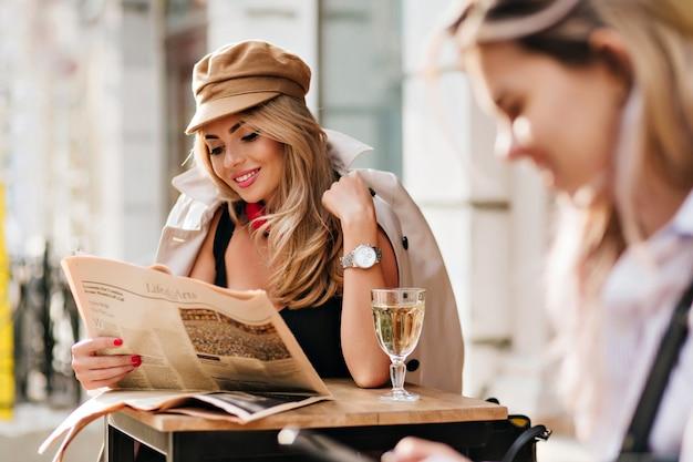 Erfreute junge frau, die lustigen artikel liest und lacht, während sie im open-air-café sitzt. fröhliches blondes mädchen, das zeitung hält und lächelt und champagner am wochenende genießt. Kostenlose Fotos