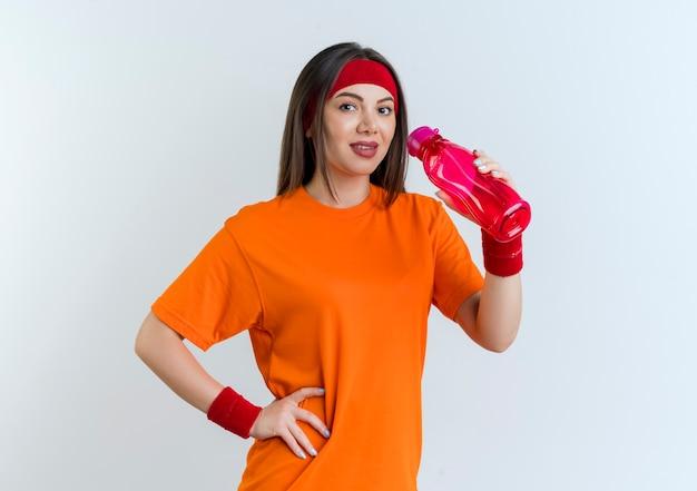 Erfreute junge sportliche frau, die stirnband und armbänder hält wasserflasche hält hand auf taille lokalisiert auf weißer wand mit kopienraum Kostenlose Fotos