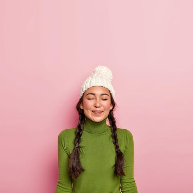 Erfreutes dunkelhaariges mädchen hält die augen geschlossen, denkt über ein angenehmes treffen mit einem freund nach, trägt einen weißen hut und einen grünen rollkragenpullover und steht an einer rosa wand Kostenlose Fotos
