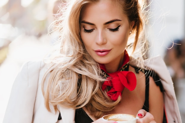 Erfreutes weibliches modell mit trendigem make-up, das nach unten schaut, während tasse cappuccino hält. nahaufnahmeporträt des europäischen blonden mädchens, das kaffeegeschmack mit geschlossenen augen genießt. Kostenlose Fotos
