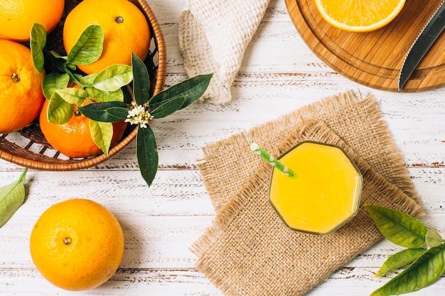 Erfrischender orangensaft neben einem korb voller orangen Kostenlose Fotos
