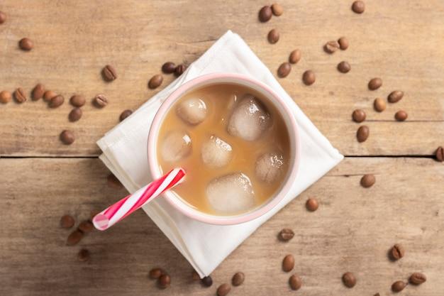 Erfrischender und belebender eiskaffee in einem glas und kaffeekörnern auf einem holztisch. konzept coffeeshop, durst stillen, sommer. flache lage, draufsicht Premium Fotos