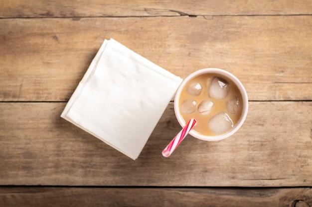 Erfrischender und verspannender eiskaffee in einem glas auf einem hölzernen hintergrund. konzept coffeeshop, durst stillen, sommer. flache lage, draufsicht Premium Fotos