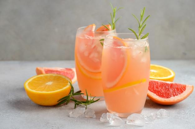 Erfrischendes zitruscocktail mit grapefruit, orange und rosmarin. Premium Fotos