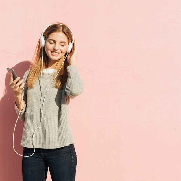 Erfüllte blonde junge frau, welche die musik am handy durch kopfhörer gegen rosa hintergrund genießt Kostenlose Fotos