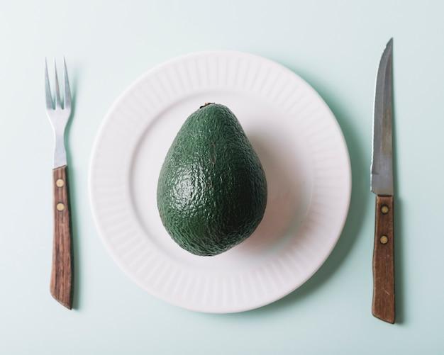 Erhöhte ansicht der avocado in der platte nahe messer und gabel auf grünem hintergrund Kostenlose Fotos