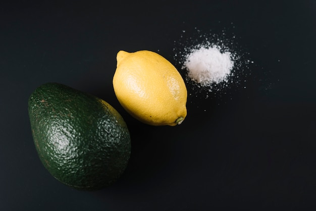 Erhöhte ansicht der avocado; zitrone und salz auf schwarzem hintergrund Kostenlose Fotos
